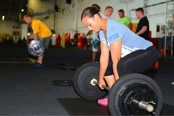 Woman lifting Barbell - Use of a back brace for lower back pain is recommended