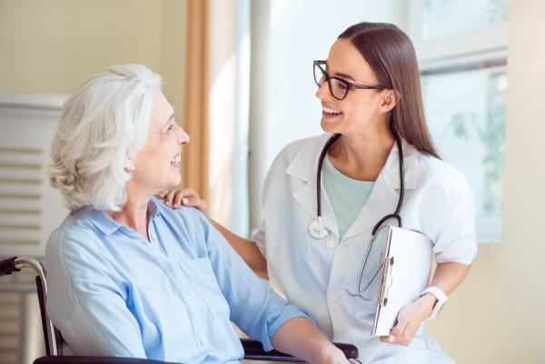 Nurse Greeting Elderly Patient In a Way That Will Help To Increase Repeat Visits From Patients
