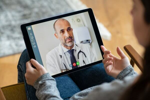Patient consulting with a doctor using a tablet computer. Increasing the use of video or telecommunication technology to communicate with patients can help to increase patient flow at your clinic
