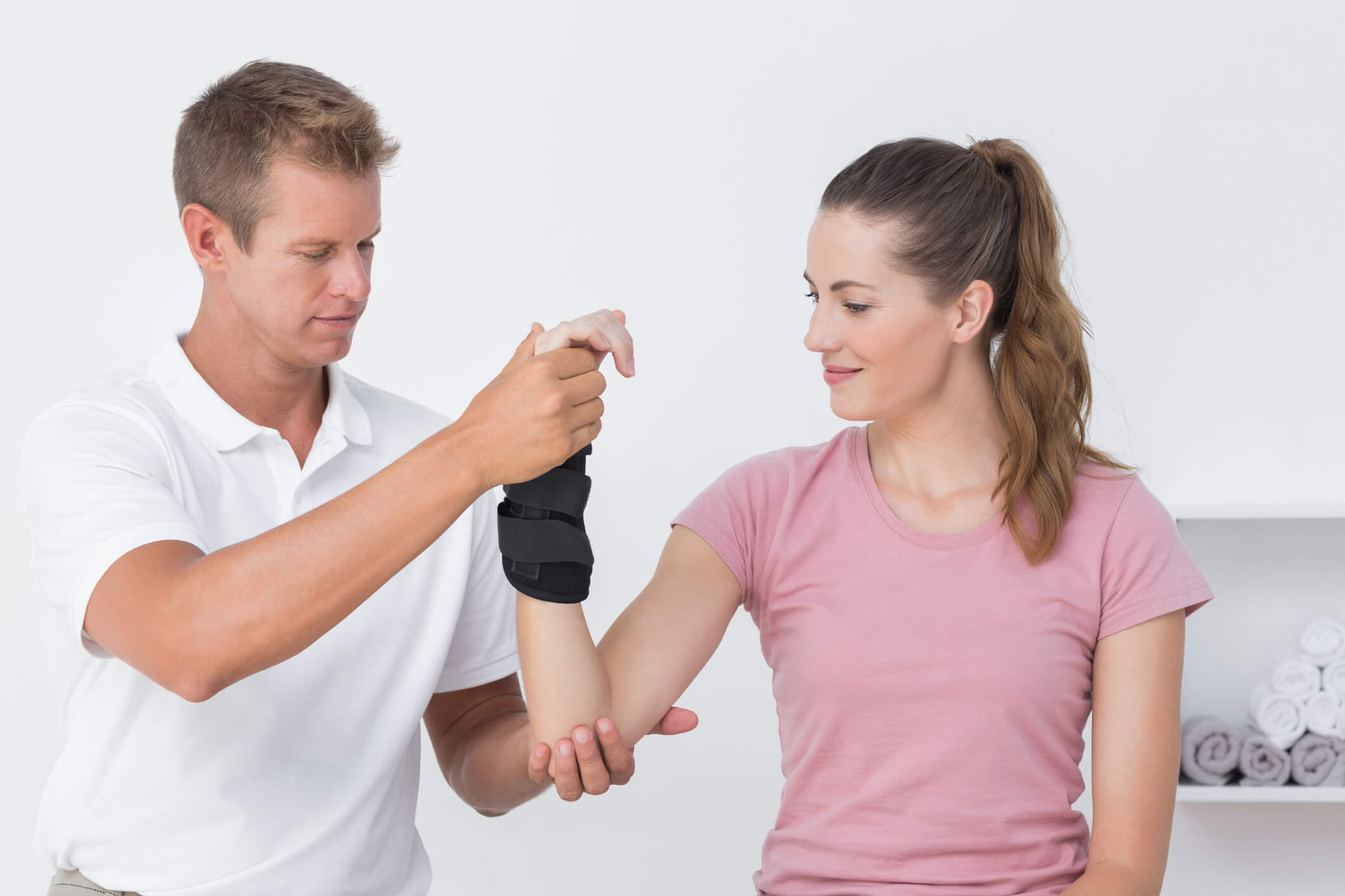 Doctor examining a female patient wearing a wrist support