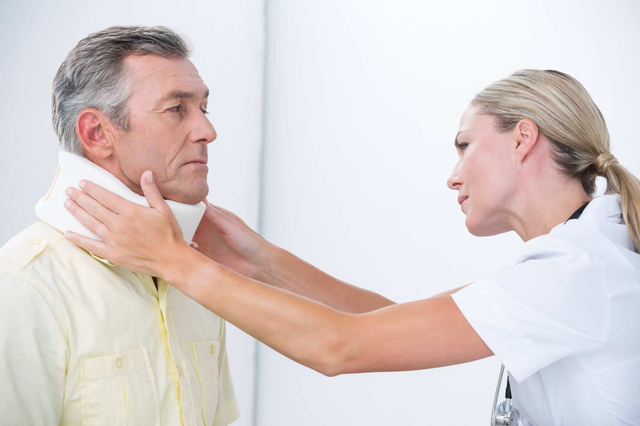Male patient being fitted with a neck brace