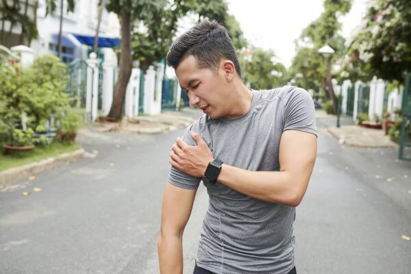 Man holding a painful right shoulder
