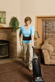 Woman using a vacuum cleaner while wearing the Mueller Adjustable Back & Abdominal Support