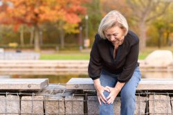 Elderly lady grabbing her knee in pain as she sits on a wall surrounding a pond after injuring herself out walking on an autumn day.