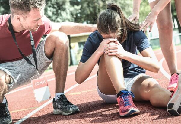Female athlete getting injured during athletic run training - Male coach taking care on sport pupil after physical accident - Team care concept with young sporty people facing mishaps casualty