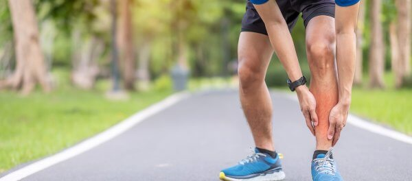 Young adult male with his muscle pain during running. runner man having leg ache due to Shin Splints.
