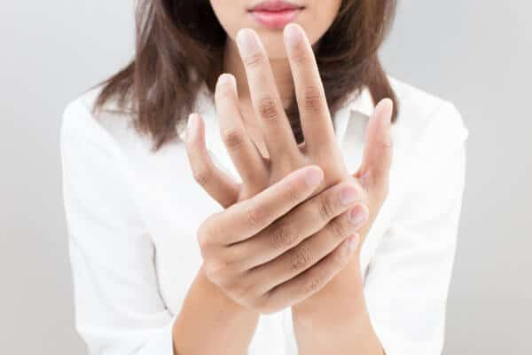 Woman experiencing acute pain in wrist or thumb