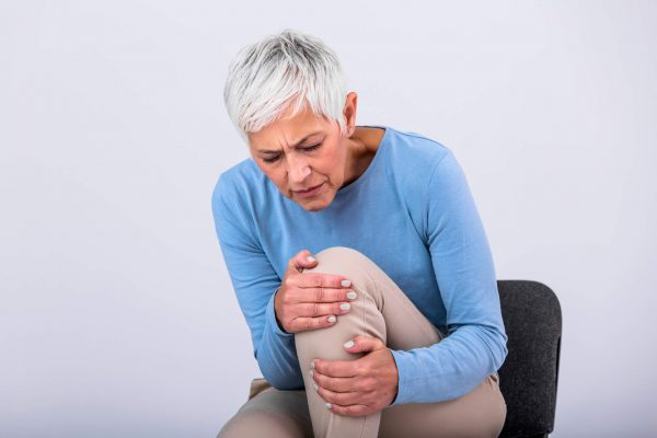 Senior woman holding the knee with pain. Old age, health problem and people concept - senior woman suffering from pain in leg at home. Elderly woman suffering from pain in knee at home.