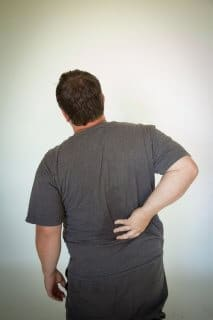 Man experiencing back pain, possibly due to a muscle problem.
