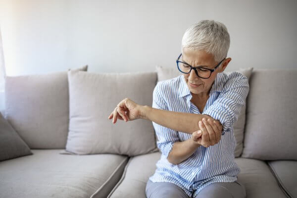 Elderly woman woman hand holding her elbow, possibly suffering from elbow arthritis.