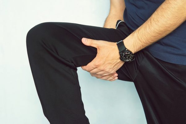 Man holding the inside of the thigh, possibly due to a thigh strain.