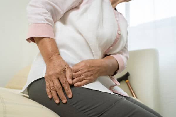 Senior woman suffering from hip pain at home,