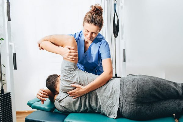 Physiotherapist treating a patient. The wages paid to your therapy team are an important component of the monthly clinic profit and loss