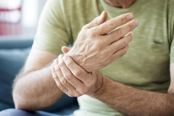 Old man suffering from wrist pain, possibly due to arthritis